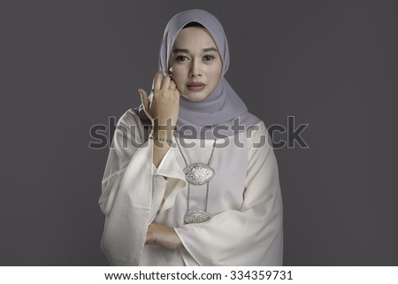 Fashion portrait of young beautiful muslim woman in modern kebaya with hijab isolated on dark grey background - stock photo
