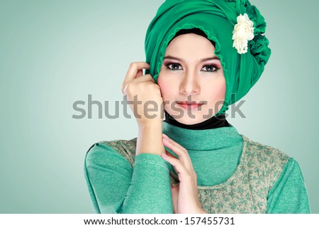 Fashion portrait of young beautiful muslim woman with green costume wearing hijab - stock photo