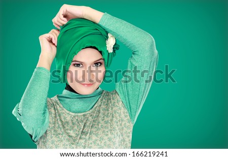Fashion portrait of young beautiful muslim woman with green costume wearing hijab isolated on green background - stock photo