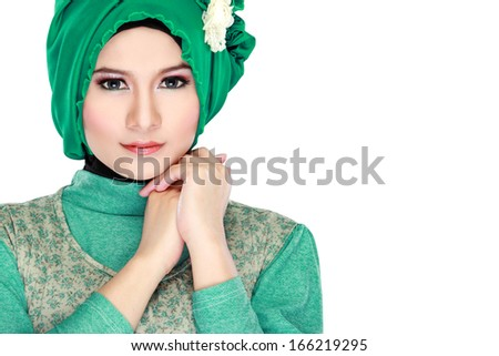Fashion portrait of young beautiful muslim woman with green costume wearing hijab isolated on white background - stock photo