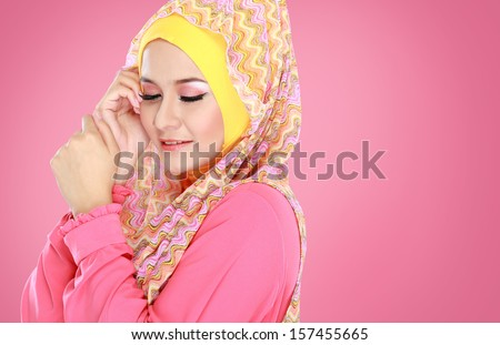 Fashion portrait of young beautiful muslim woman with pink costume wearing hijab - stock photo