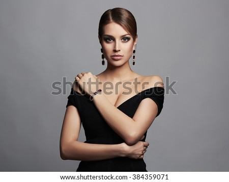 fashion portrait of young beautiful sexy woman in jewelry.Beauty girl with short hair and make-up.elegant lady in black dress - stock photo