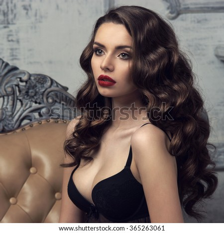 Fashion portrait of young beautiful sexy woman with long wavy hair. Pretty girl sitting in black bra or lingerie in luxury interior.