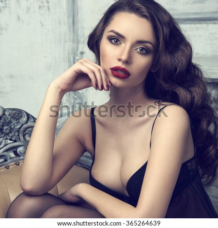 Fashion portrait of young beautiful sexy woman with long wavy hair. Pretty girl sitting in black bra or lingerie in luxury interior. Fashion style toned colors portrait - stock photo