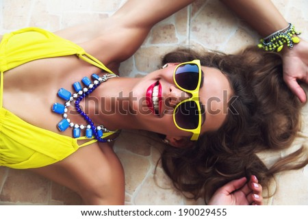 Fashion portrait of young beautiful woman lying on the floor, wearing bright sunglasses bikini and jewelry, laughing and have summer mood. - stock photo