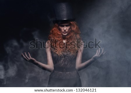 fashion portrait of young beauty woman wearing hat on smoky background - stock photo