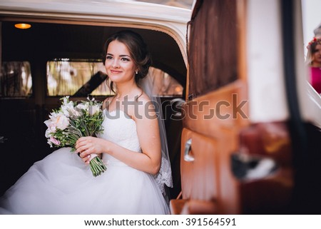 Fashion portrait of young bride with white dress with bouquet near retro car in spring - stock photo