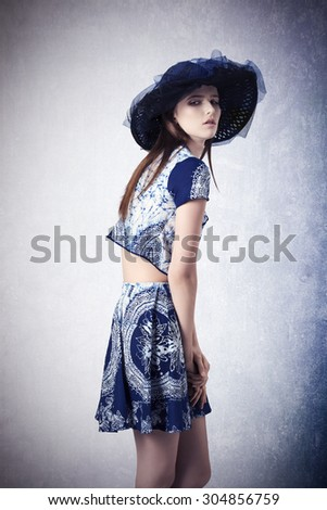 fashion portrait of young brunette girl with long hair, lovely hat and trendy summer clothes. Wearing skirt and top  - stock photo