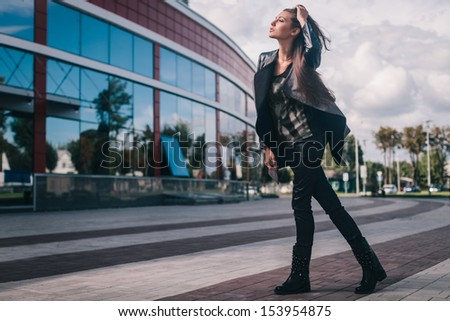 Fashion portrait of young brunette in full length on street