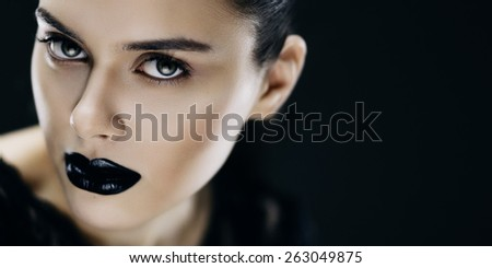 Fashion portrait of young brunette woman with black lips. Shallow depth of field - stock photo