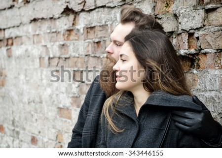 Fashion portrait of young couple, autumn outdoor against obsolete brick wall, image toned and noise added. Hipster man with beard and moustache embracing his charming girlfriend. - stock photo