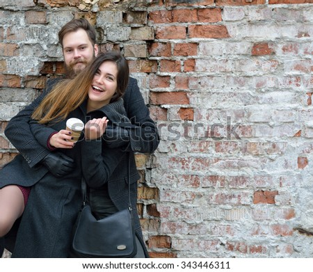 Fashion portrait of young couple drinking coffee in autumn outdoor against obsolete brick wall, image toned and noise added. Hipster man with beard and moustache  - stock photo
