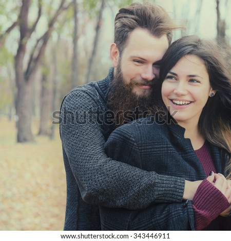 Fashion portrait of young couple have fun in autumn park outdoor, image toned and noise added. Hipster man with beard and moustache embracing his beautiful happy smiling girlfriend outside. - stock photo