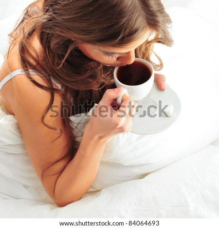 Fashion portrait of young elegant woman in bed at she`s apartment drinking coffee
