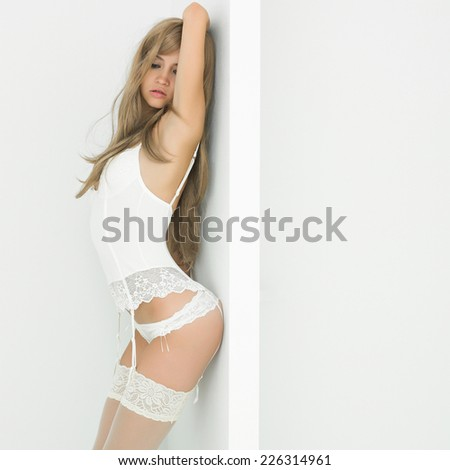 Fashion portrait of young elegant woman in bedroom - stock photo