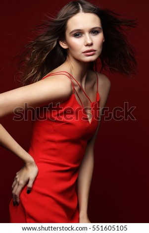 Fashion portrait of young elegant woman in red cocktail dress. Red background, blowing long hair