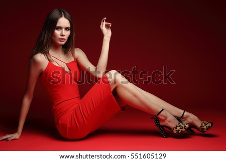 Fashion portrait of young elegant woman in studio. Red short cocktail dress, red background
