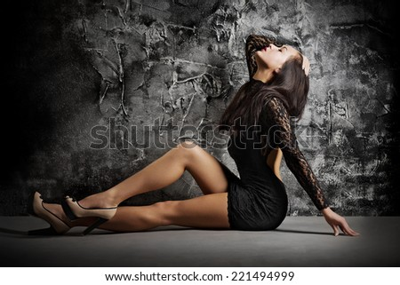 Fashion portrait of young girl on grey wall