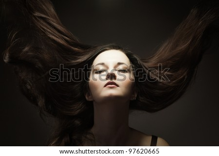 Fashion portrait of young gorgeous brunette with hair in motion
