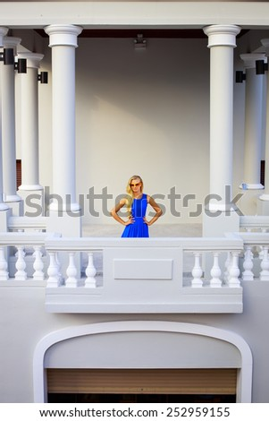 Fashion portrait of young gorgeous woman in a blue dress and sunglasses. Pretty blonde woman posing on a vintage balcony. - stock photo