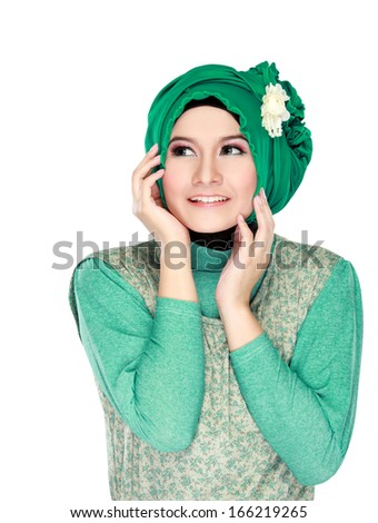 Fashion portrait of young happy beautiful muslim woman with green costume wearing hijab and looking up isolated on white background - stock photo