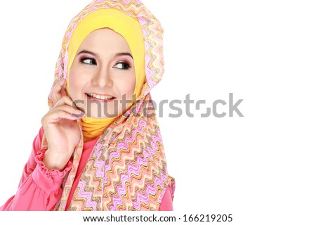 Fashion portrait of young happy beautiful muslim woman with pink costume wearing hijab and looking at copy space - stock photo