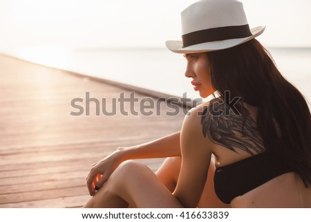 Fashion portrait of young hipster woman with hat,retro style color tones,full pink lips,no make up,natural colors,Attractive young woman enjoying her time outside sunset in sunset background.white  - stock photo