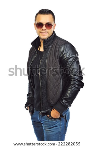 Fashion portrait of young man in jeans and black jacket posing on white background - stock photo