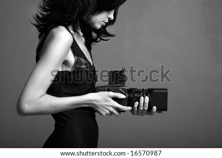 Fashion portrait of young photographing lady. Black and white photo - stock photo