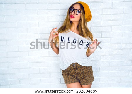Fashion portrait of young pretty hipster woman with blonde hairs and big full bright lips wearing stylish outfit, denim swag shorts hat glasses and t shirt with funny print.urban wall background.  - stock photo