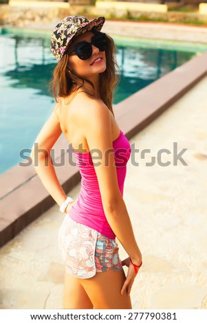Fashion portrait of young sensual brunette woman with long amazing curled hairs, natural make up,posing outdoor in summer got sunny day, wearing bright neon sport clothes back back and sunglasses. - stock photo