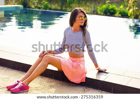 Fashion portrait of young sensual brunette woman with long amazing hairs, natural make up.Amazing and sunshine model in summer outfit sitting near pool in round sunglasses. - stock photo