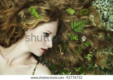 Fashion portrait of young sensual woman in garden - stock photo