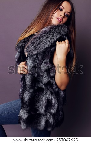 Fashion portrait of young sexy beautiful girl with long hair and bright make-up wearing a black lingerie,jeans,hight shoes and fur coat, moving and posing at studio