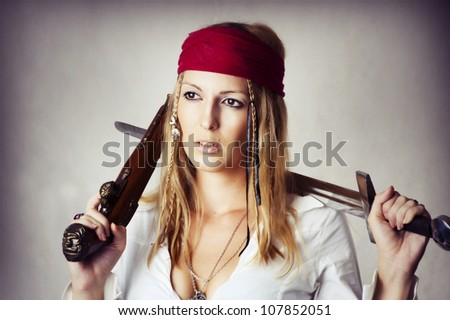 Fashion portrait of young sexy blond woman in pirate style with old handgun and medieval sword - stock photo