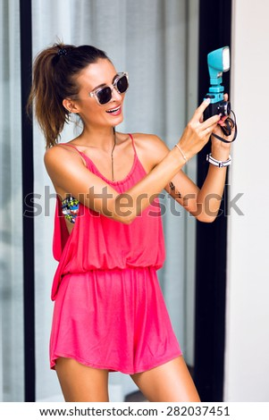 Fashion portrait of young sexy hipster photographer  woman, wearing bright summer stylish outfit, making photos on vintage camera. - stock photo