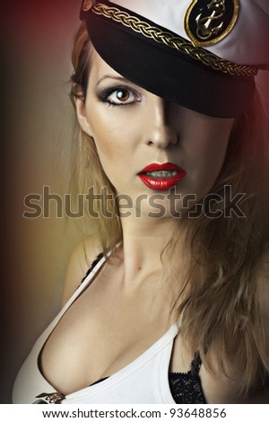 Fashion portrait of young sexy woman with red lips and captain cap