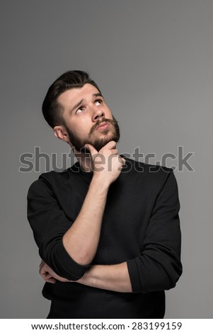 Fashion portrait of young  thoughtful  man in black  poses over gray background. hand man scratching his beard. gaze directed upwards - stock photo