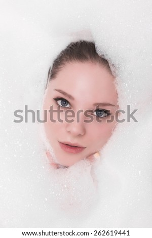 Fashion portrait of young woman floating in Spa filled with foam - stock photo