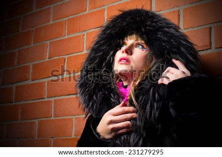 Fashion portrait of young woman on brick wall background - stock photo