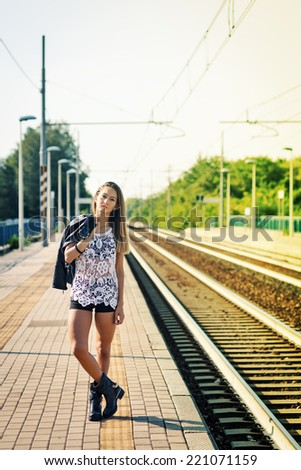 Fashion portrait of young woman outdoors in train station. Filtered image. - stock photo