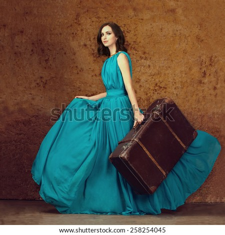 Fashion portrait of young woman walking with old suitcase. Travel concept - stock photo