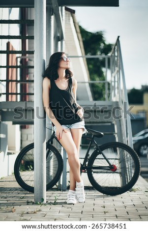 Fashion portrait of young woman with bicycle