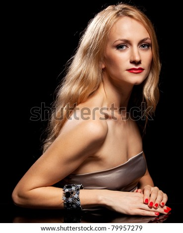 Fashion portrait of young woman with long hair on black background