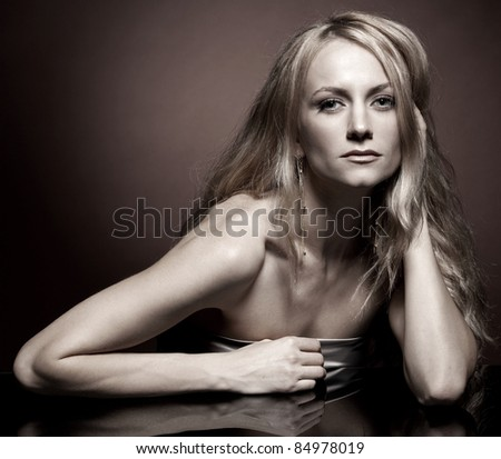 Fashion portrait of  young woman with long hair on brown background