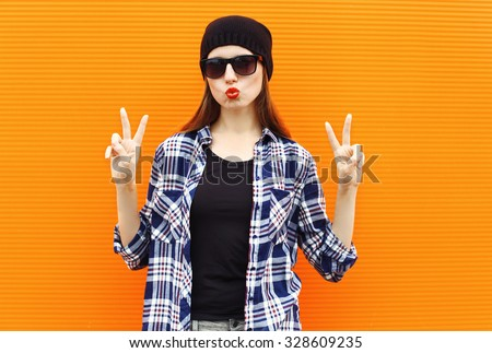 Fashion portrait pretty cool girl wearing a black hat, sunglasses and shirt over colorful background - stock photo