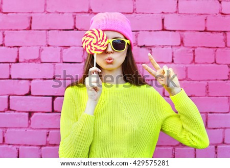 Fashion portrait pretty cool girl with lollipop having fun over colorful pink background - stock photo