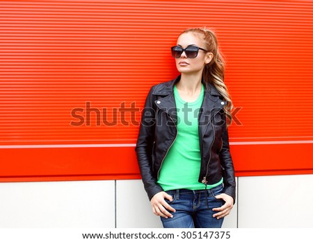 Fashion portrait pretty woman in rock black style, wearing a sunglasses and leather jacket against the red background - stock photo