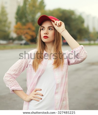 Fashion portrait pretty young girl wearing a shirt and red cap outdoors - stock photo