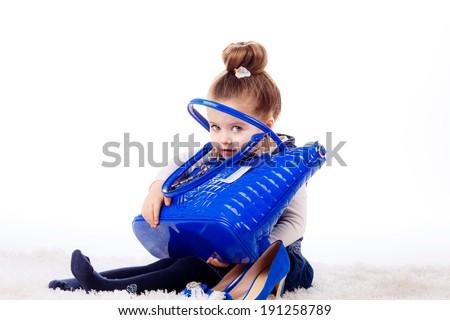 fashion portrait. Stylish little girl with shoes and bag mom. isolated on white background. fashionista, shopping - stock photo